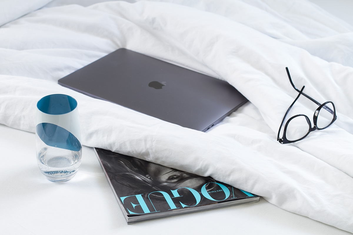 Water - The Elixir of Life - Blog Post on Lifetime-pieces.com Leonardo Glass Vogue Magazine Saint Laurent Glasses MacBook Pro on Bed with white Linen