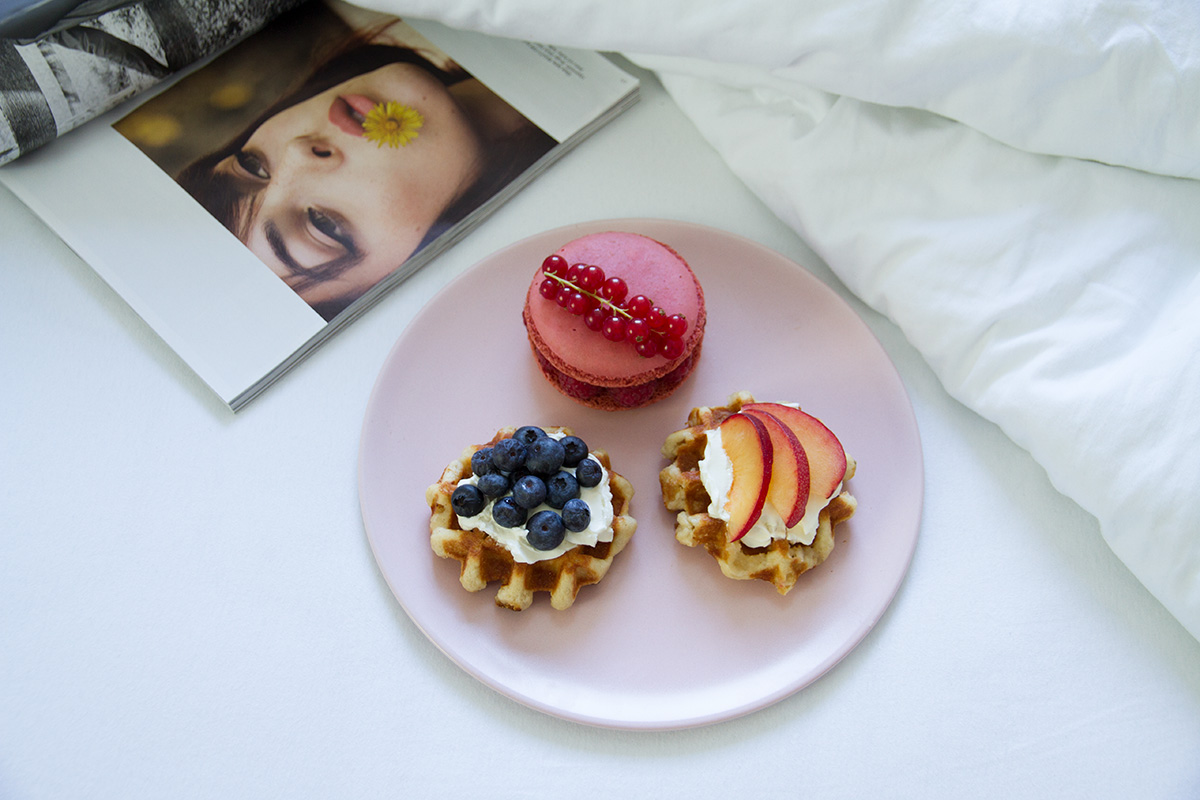 breakfast in bed pink plate waffles with cream cheese and fruits macaron white linen open magazine