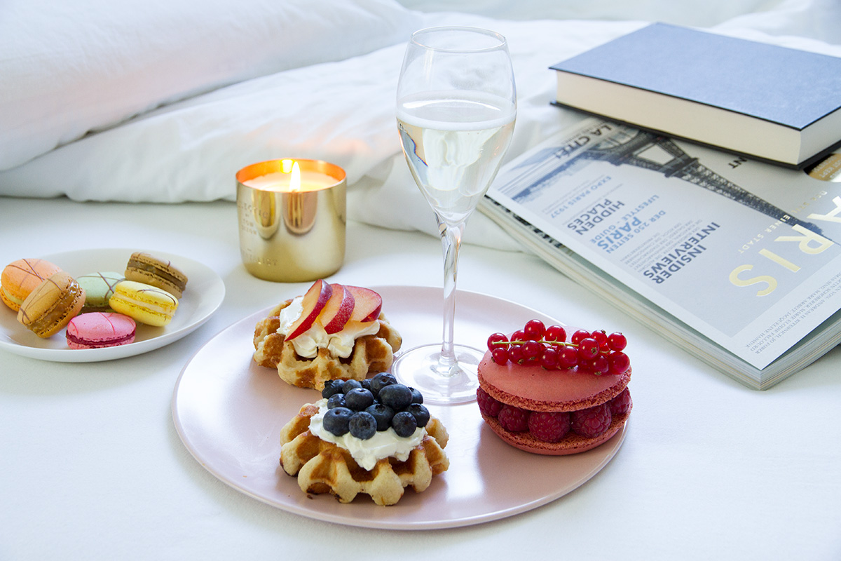 breakfast in bed plates waffles with cream cheese and fruits macarons glass of champagne white linen book magazine scented candle
