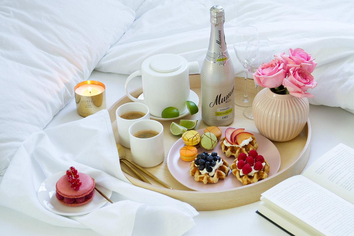 breakfast in bed tray waffles macarons fruits coffee bottle of champagne vase pink flowers white linen open book scented candle
