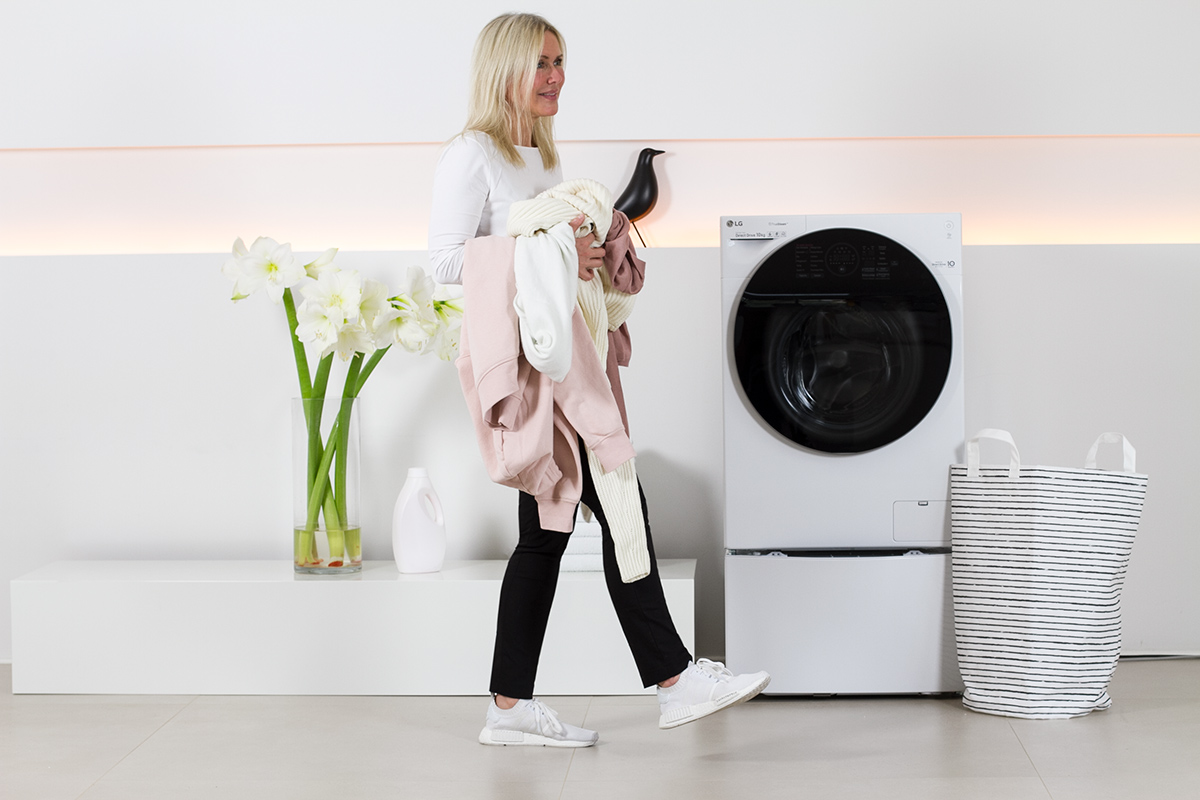 women walking in front of a washer, washing machine, holding laundry in her hands, white flowers, liquid laundry detergent bottle, picture from LG TwinWash blog post on lifetime-pieces.com