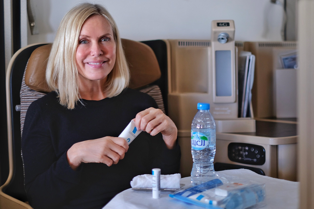 woman sitting in airplane, Etihad business class, holding a La Roche-Posay hand cream, bottle of water, blog post about long-haul flights on Lifetime-pieces.com