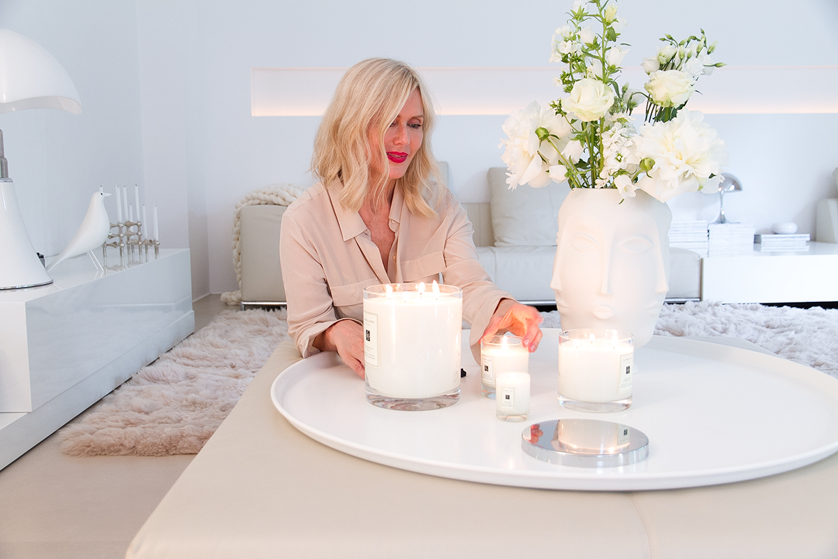 Jo Malone London, living in a scented home, blond woman lightning scented candles in a living room