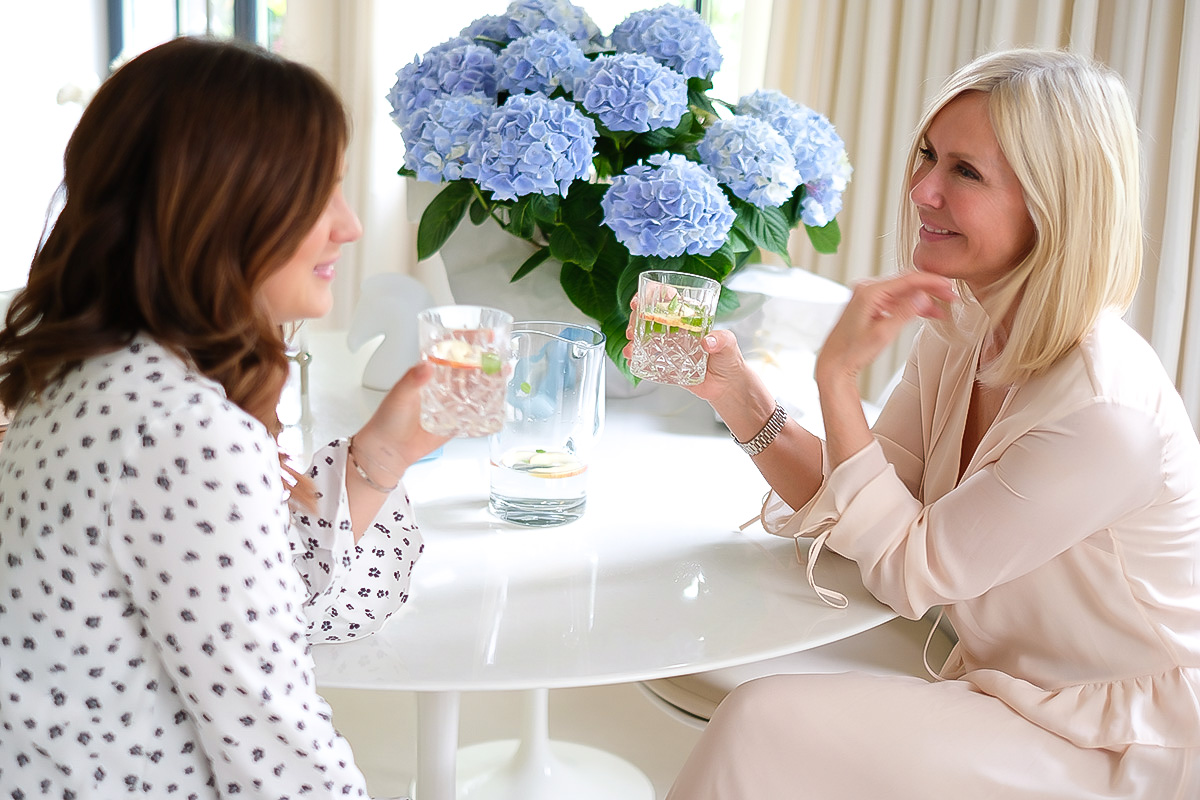 2 Women, Mother and Daughter, sitting on a table, holding glasses of e water in their hands, talking, Mother's Day Blog post on Lifetime-pieces.com