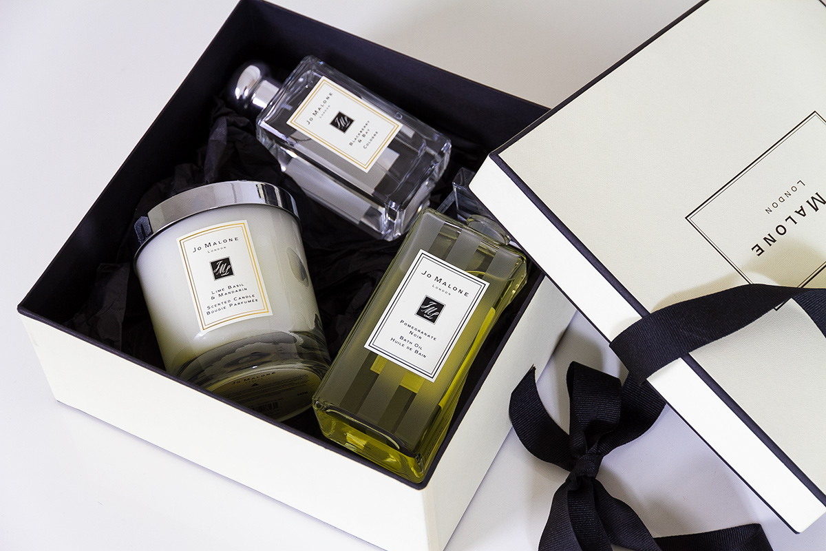 Jo Malone London, living in a scented home, open cream signature gift box and black ribbon, inside the box are Jo Malone products, a scented candle, a bath oil and a cologne
