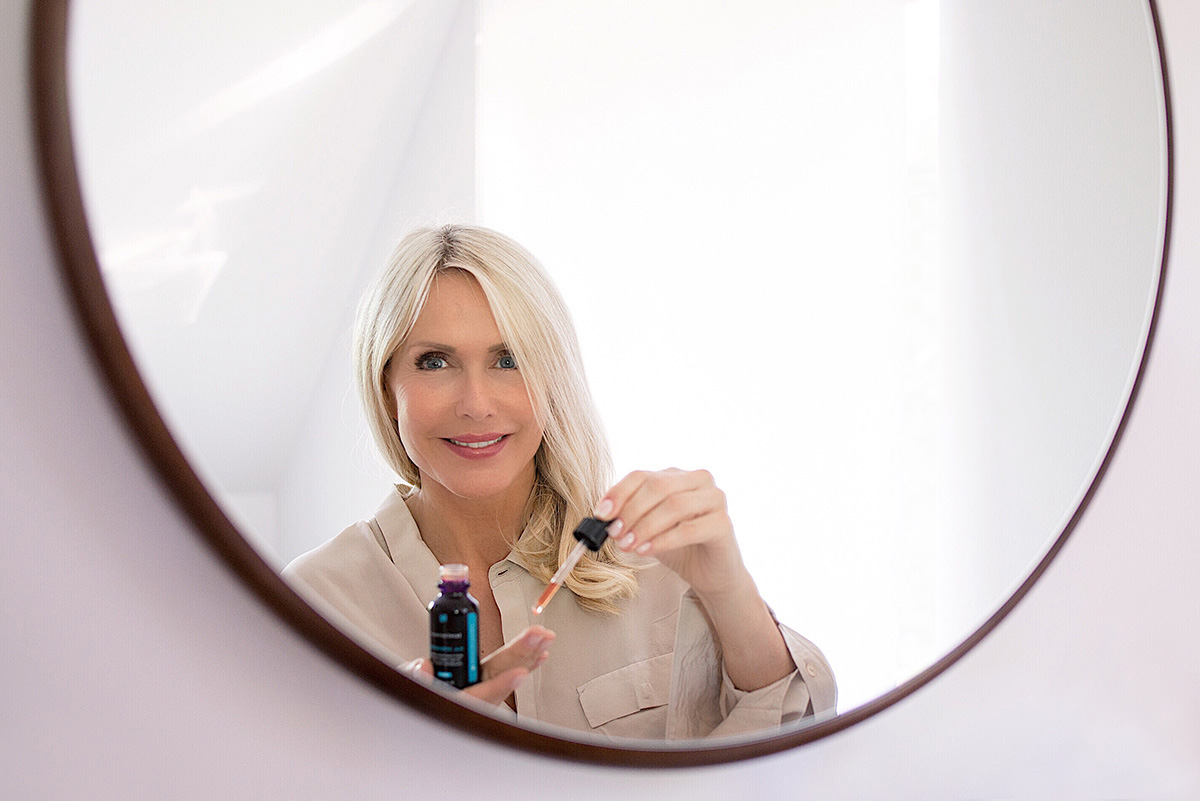 Woman in a mirror holding SkinCeuticals Hyaloronic Acid from SkinCeuticals blog post on Lifetime-Pieces.com