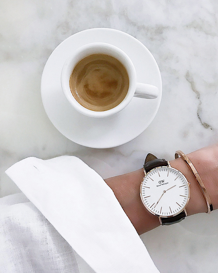 Daniel Wellington cuff and classic watch arm white shirt marble table with coffee Blog post on Lifetime-pieces.com