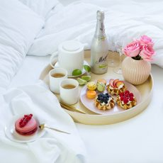 breakfast in bed tray waffles macarons fruits coffee bottle of champagne vase pink flowers white linen