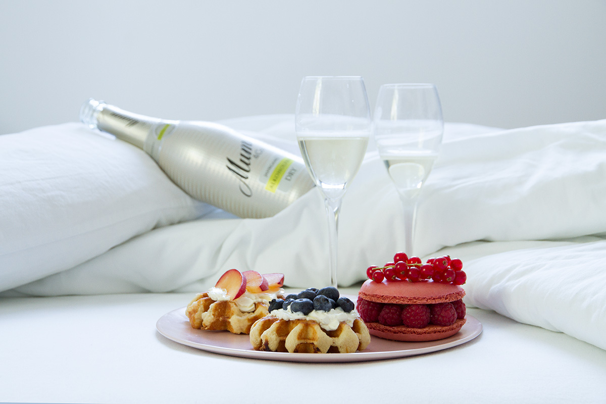 breakfast in bed plates waffles with cream cheese and fruits macaron two glasses bottle of champagne white linen