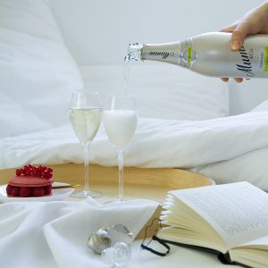 breakfast in bed hand holding a bottle filling two glasses of champagne macarons