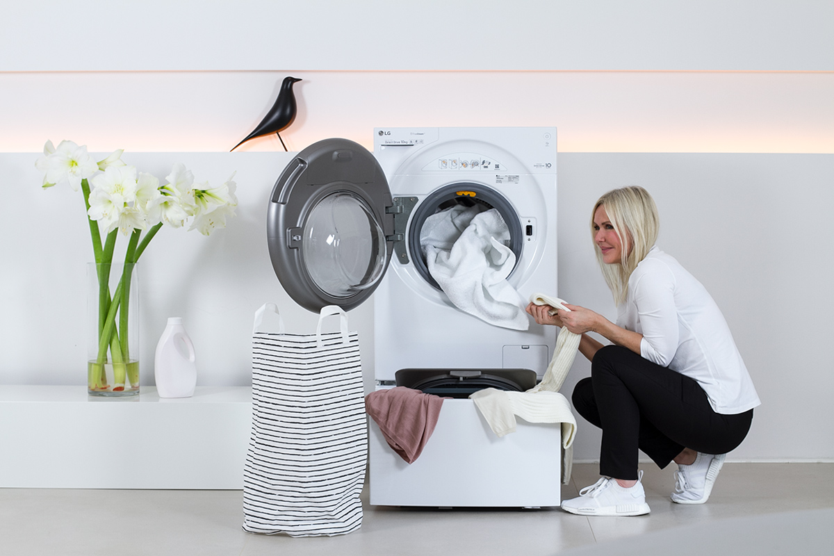 women in squatting positions beside a washer, washing machine, laundry, folded, white flowers, liquid laundry detergent bottle, white flowers, picture from LG TwinWash blog post on lifetime-pieces.com