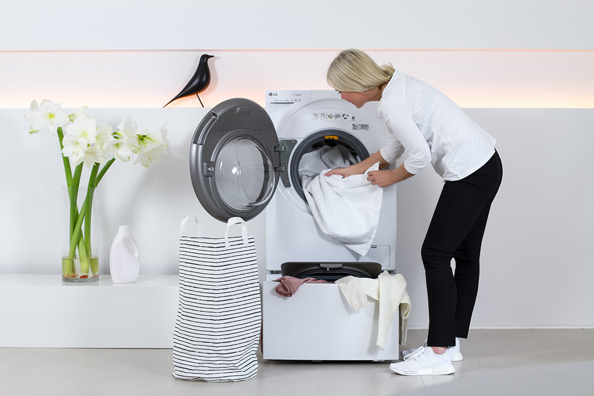 women standing beside a washer, washing machine, laundry, white flowers, liquid laundry detergent bottle, picture from LG TwinWash blog post on lifetime-pieces.com