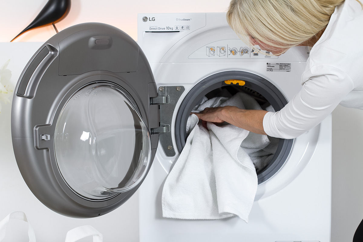 women filling a washing machine with laundry, picture from LG TwinWash blog post on lifetime-pieces.com