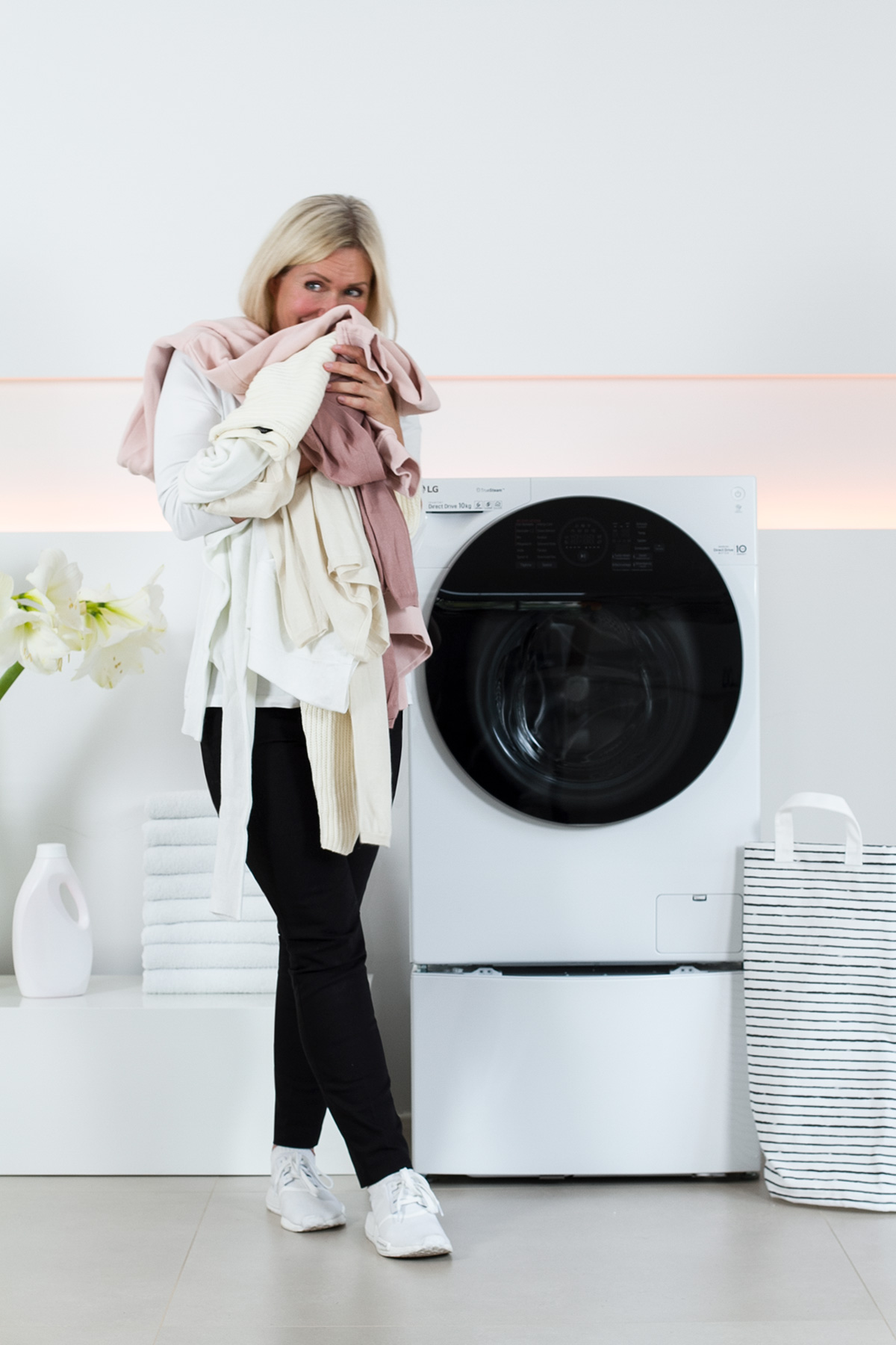 women standing in front of a washer, washing machine, holding laundry in her hands, white flowers, liquid laundry detergent bottle, picture from LG TwinWash blog post on lifetime-pieces.com