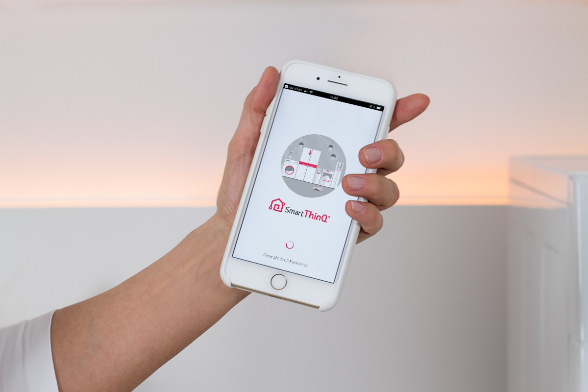 hand holding an iPhone with the LG smartthinQ App on it, picture from LG TwinWash blog post on lifetime-pieces.com