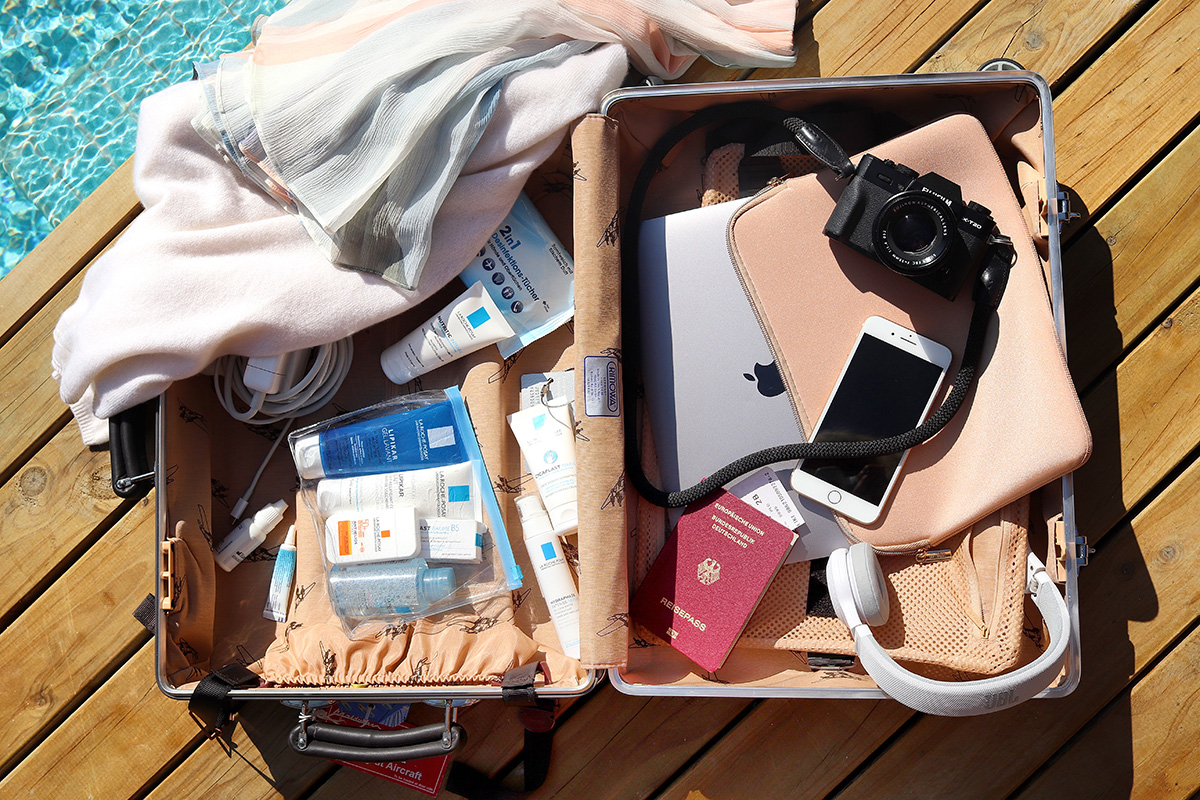 Opened Suitcase, cabin trolley, at a pool, inside camera, iphone, passport, headphones, apple laptop, sweater, La Roche-Posay travel set, blog post about long-haul flights on Lifetime-pieces.com