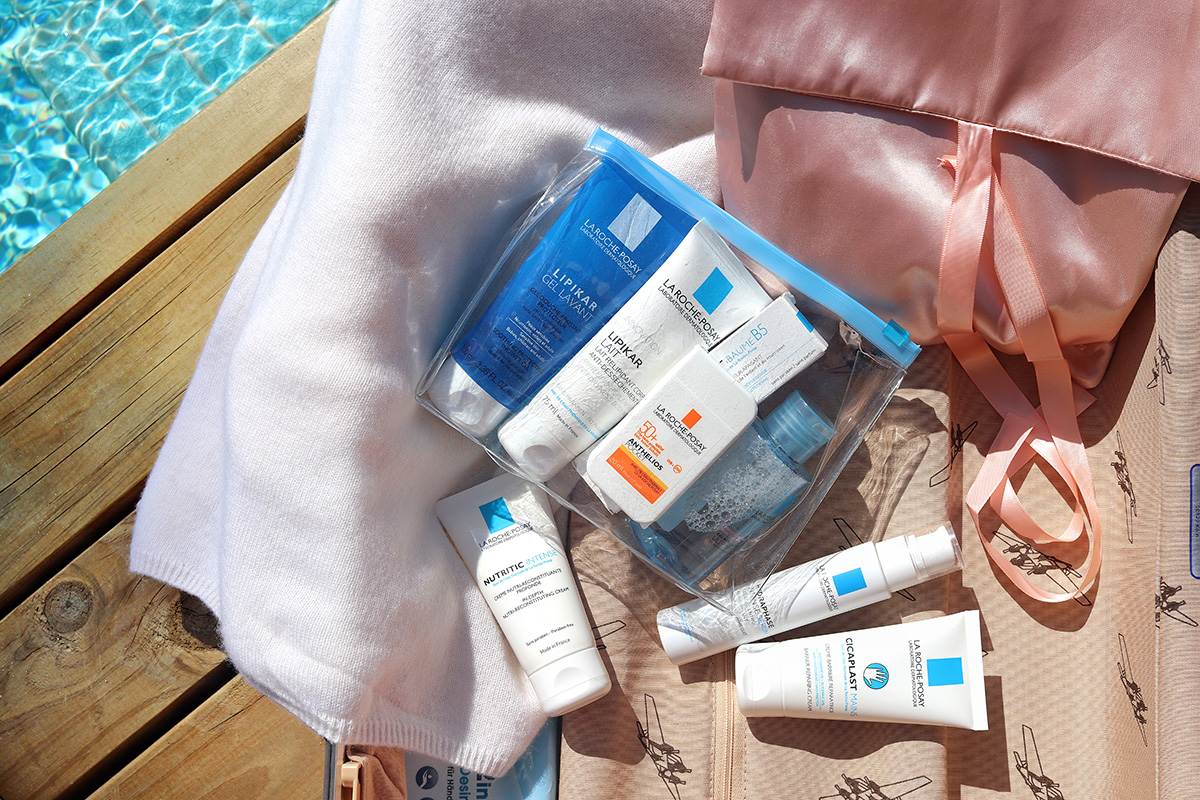 La Roche-Posay Travel Kit lying on wooden floor at a pool, blog post about long-haul flights on Lifetime-pieces.com