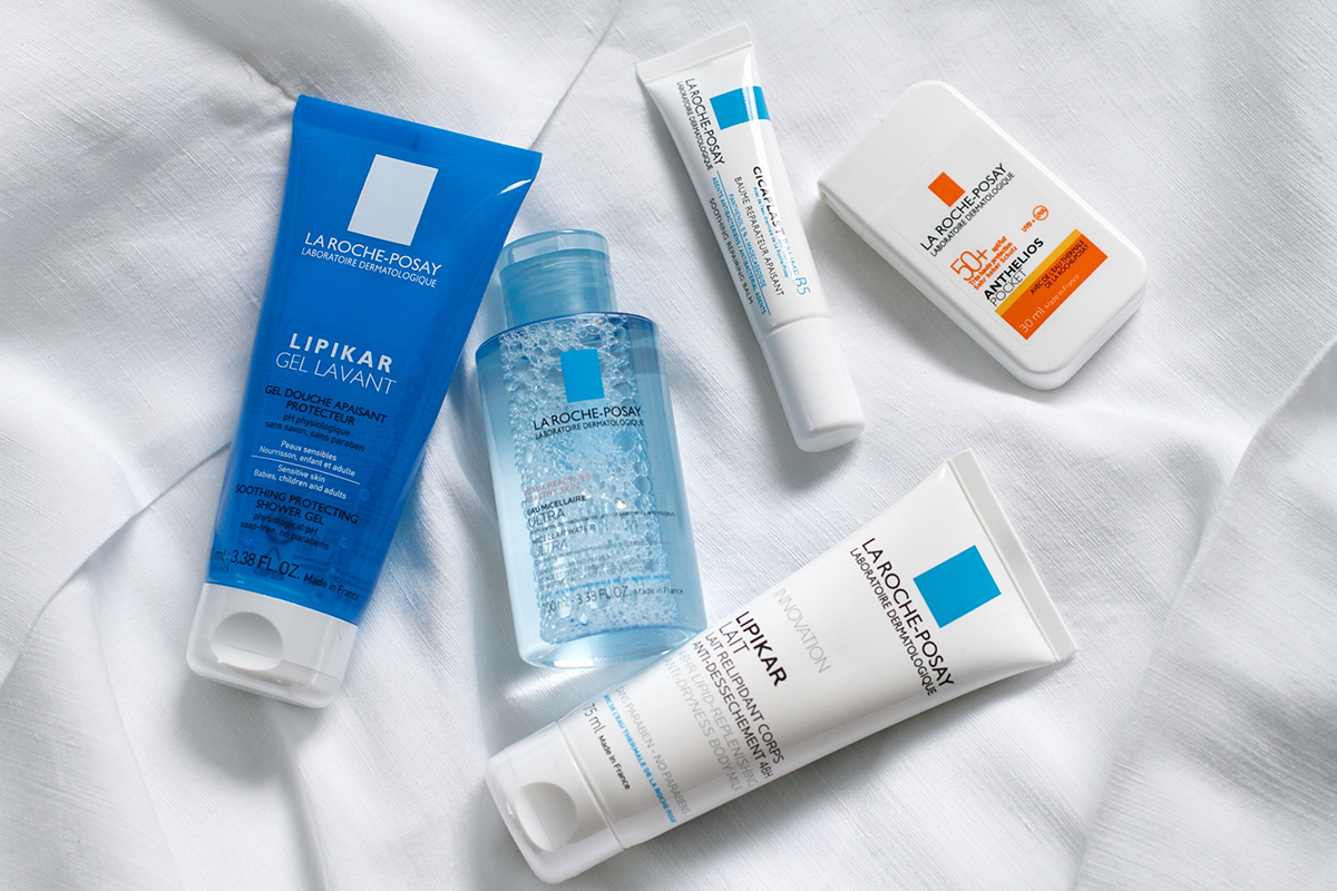 Flatlay of La Roche-Posay travel set, Anthelios sunscreen, Lipikar body lotion, Lipikar shower gel, Micellar water, Cicaplast Baume, blog post about long-haul flights on Lifetime-pieces.com