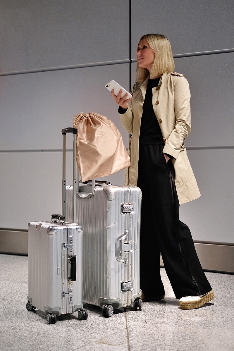 woman, suitcases, cabin trolley, rimowa, waiting, airport, blog post about long-haul flights on Lifetime-pieces.com