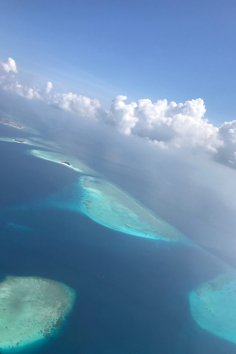 Maldive islands, Atolls, view from above, out of a plane, white clouds, blue sky, blog post about Maldives on lifetime-pieces.com