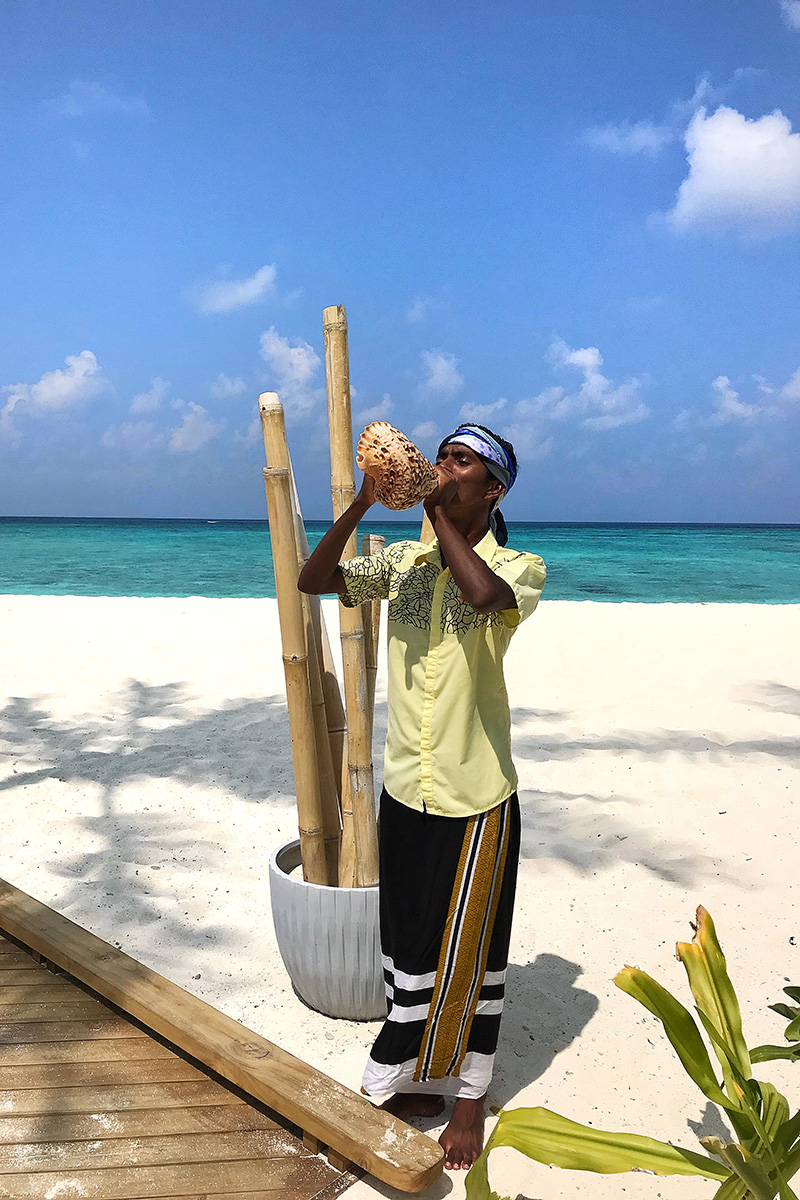 Fushifaru, beach, sand, man blowing a shell,, sand, water, Indian Ocean, sea, blue sky, white clouds, blog post about Maldives on lifetime-pieces.com