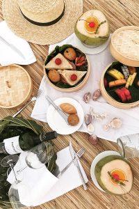 Fushifaru, picnic, straw hat, fruits, food, coconuts, glasses, bottle of wine, bread, sandwiches, shells, blog post about Maldives on lifetime-pieces.com