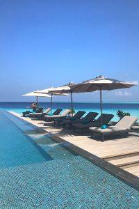 Fushifaru, infinity pool, sunshades, sun beds, blue sky, Indian Ocean, sea, pool water, blog post about Maldives on lifetime-pieces.com