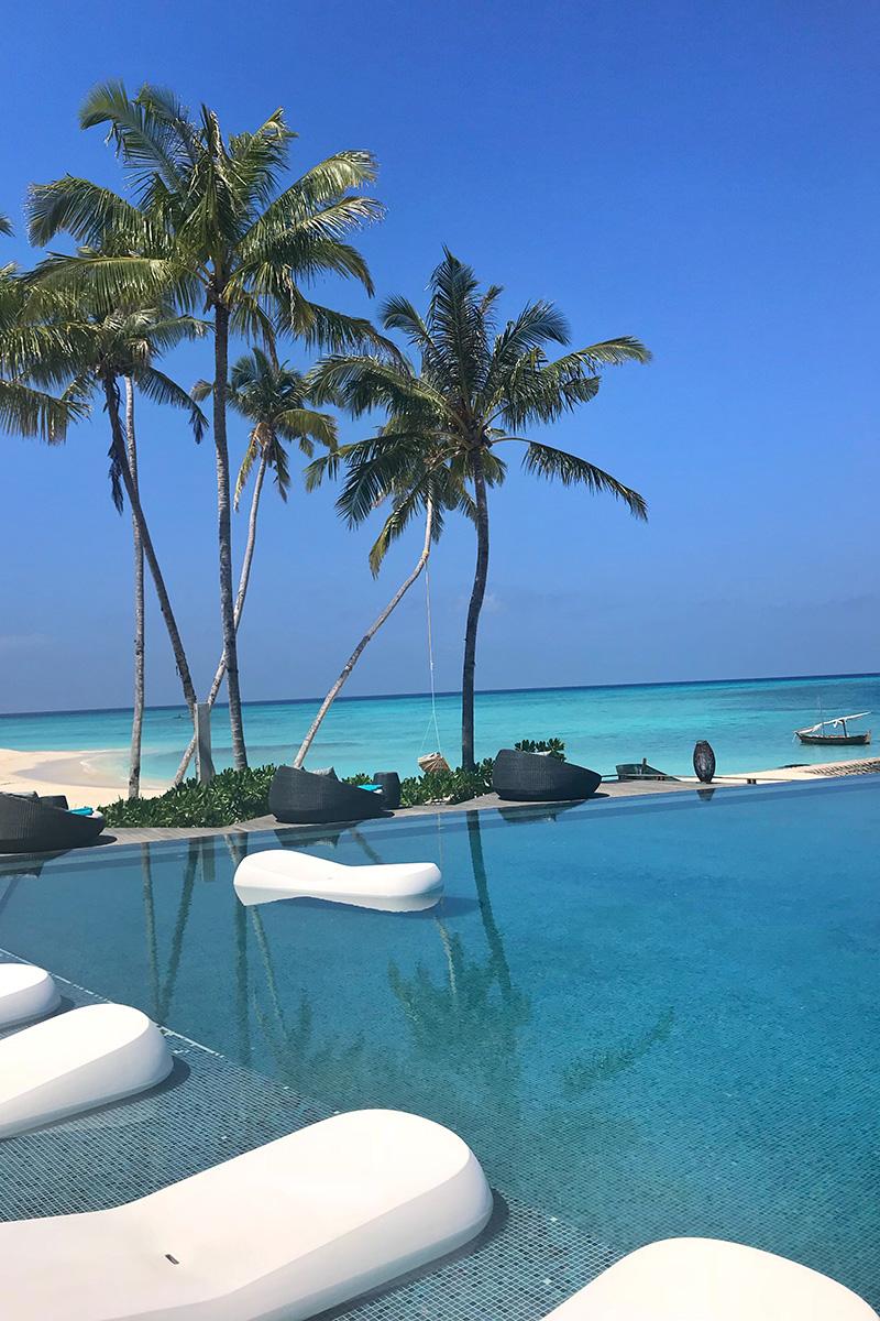 Fushifaru, infinity pool, sun beds, blue sky, Indian Ocean, sea, pool water, blog post about Maldives on lifetime-pieces.com
