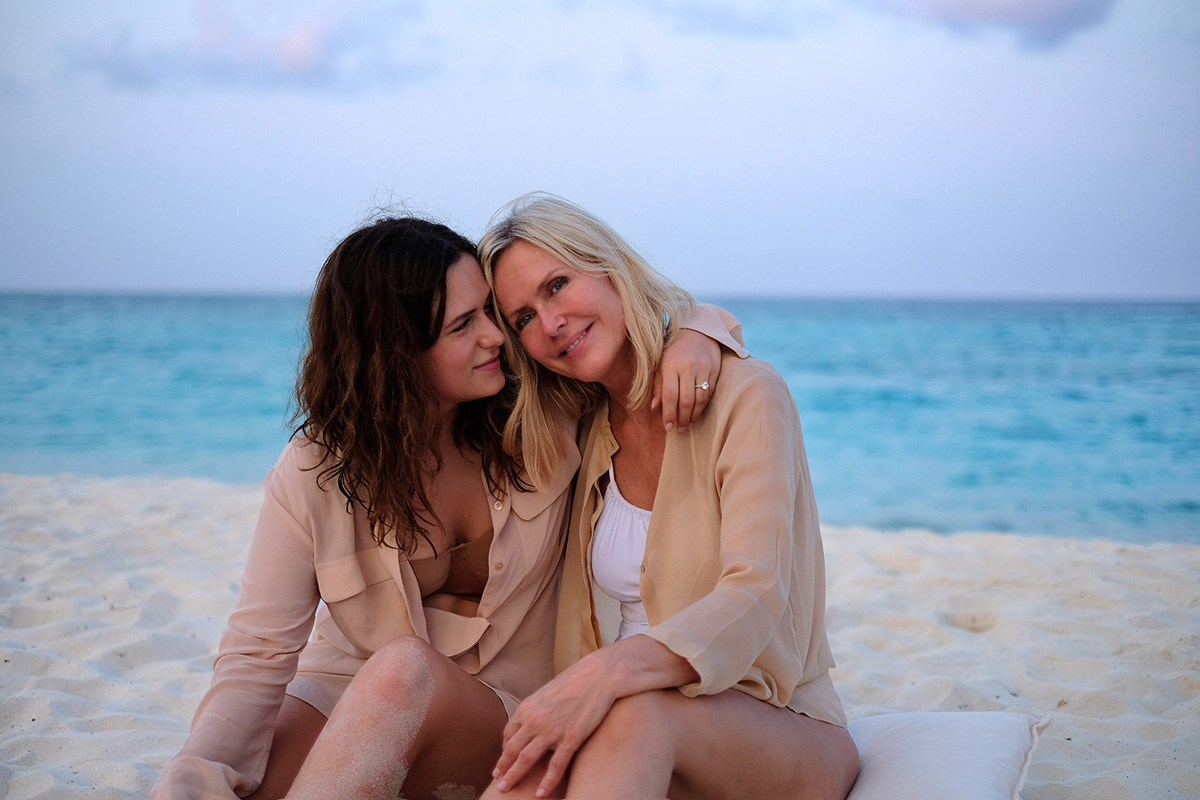 mom and daughter trip to Maldives, 2 women with shirts sitting in the sand at the beach, blog post about Maldives on lifetime-pieces.com