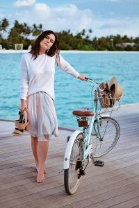 women with a bicycle, standing on a plank, in front of the Indian Ocean, holding shoes in er hand, blog post about Maldives on lifetime-pieces.com