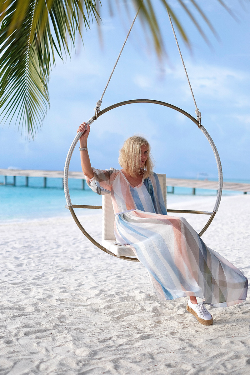 Kamndima, woman sitting in a swing set, beach, palms, white sand, sea, Indian ocean, blue sky, blog post about Maldives on lifetime-pieces.com