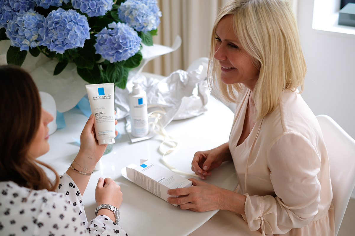 2 Women, Mother and Daughter, sitting on a table, holding La Roche-Posay Lipikar Lotion in their hands, talking, Mother's Day Blog post on Lifetime-pieces.com