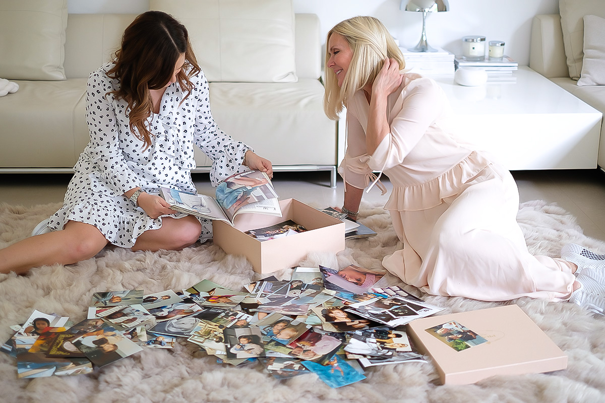 2 Women, Mother and Daughter, sitting on a rug, holding old pictures in their hands, talking, Mother's Day Blog post on Lifetime-pieces.com