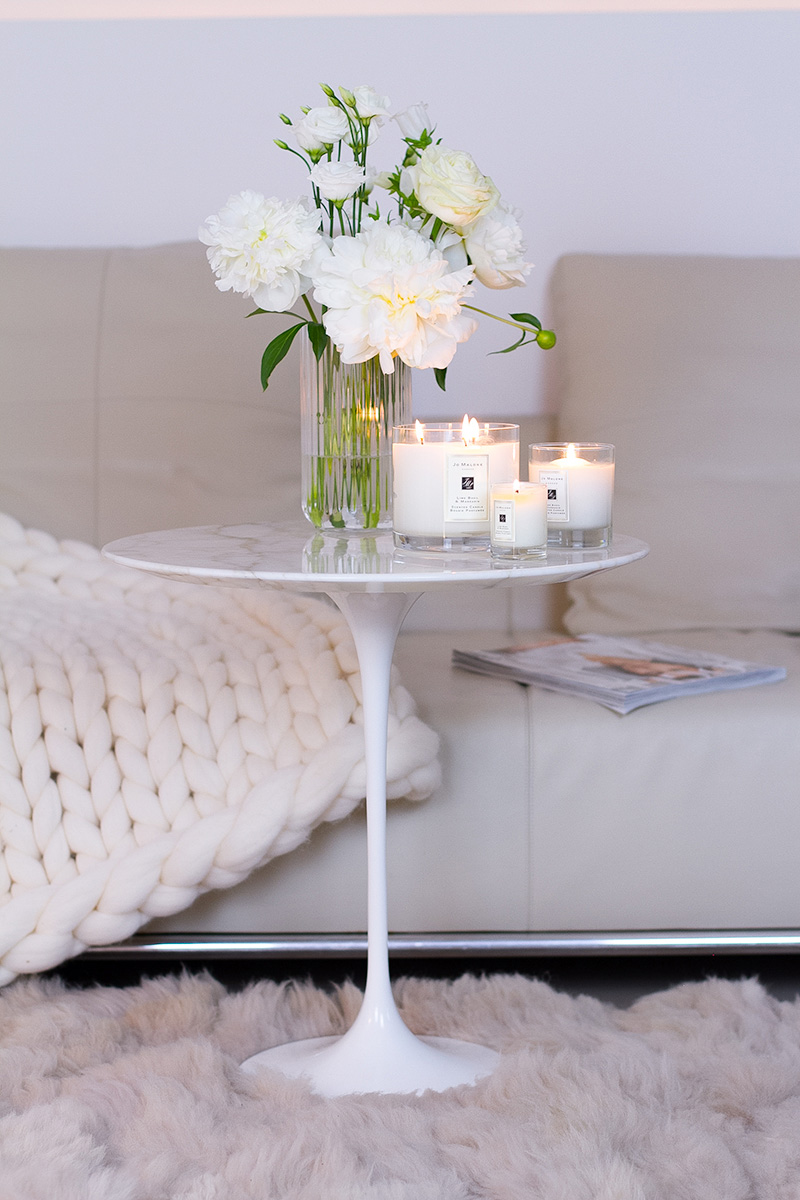 Jo Malone London, living in a scented home, white Saarinen side table , three scented candles, a vase with white peonies flowers on the table