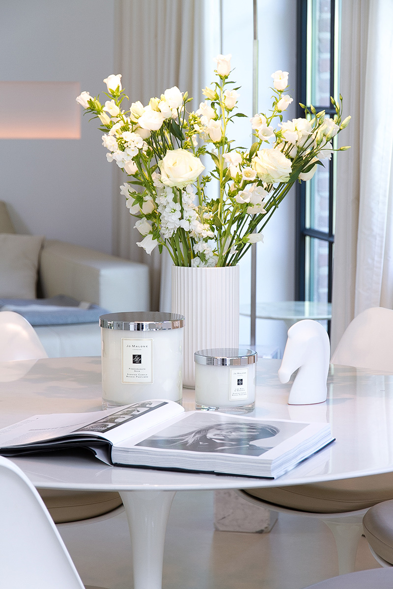 Jo Malone London, living in a scented home, white Saarinen table with Tulip chairs, scented candles, a vase with white spring flowers and a coffee table book on the table