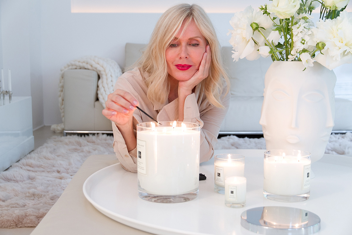 Jo Malone London, living in a scented home, woman lightning scented candles in a living room