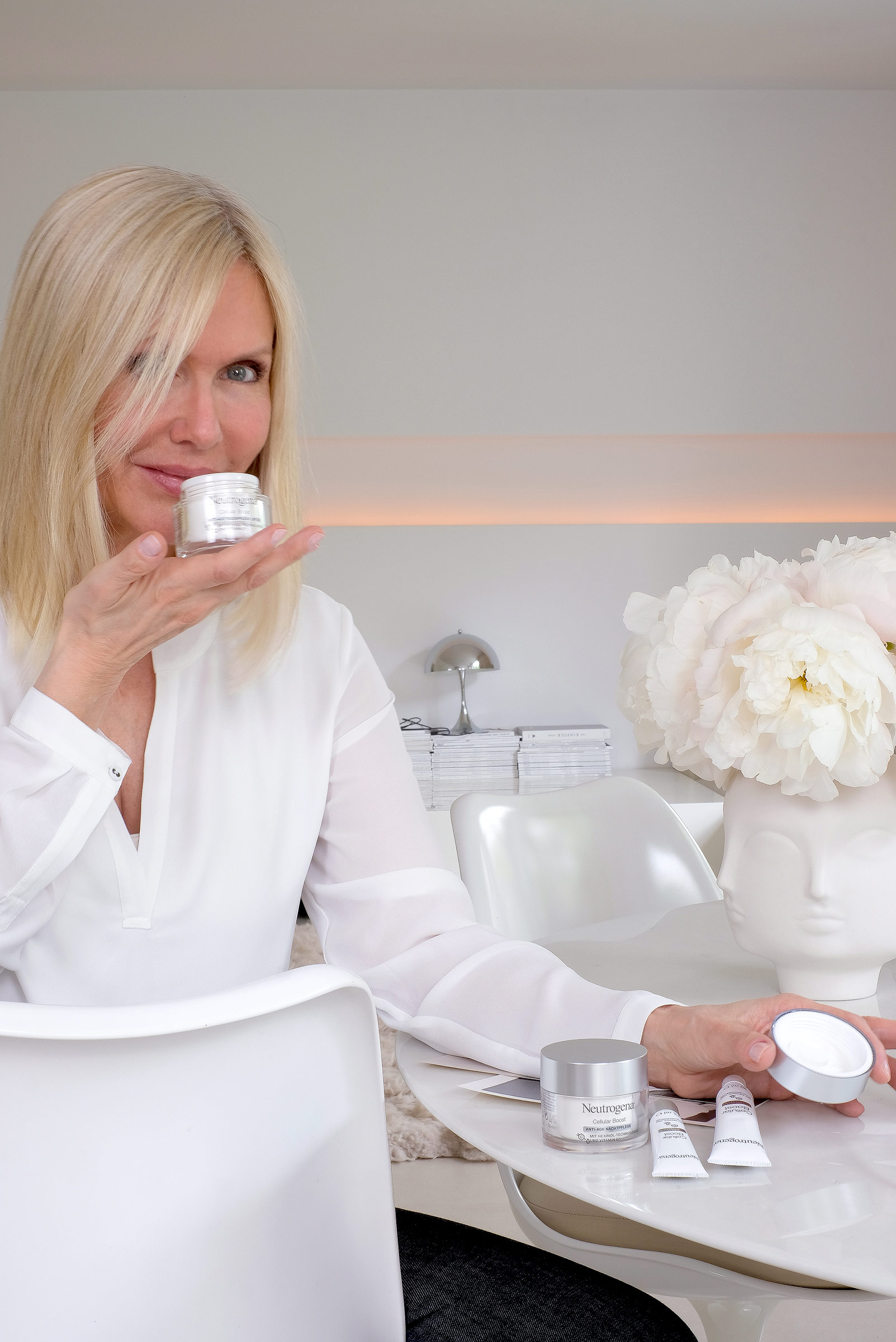blonde woman sitting on a chair, table, holding Neutrogena cellular boost skincare product in her hand