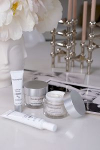 neutrogena, cellular boost, products, skincare, on a table, flowers, candle holders