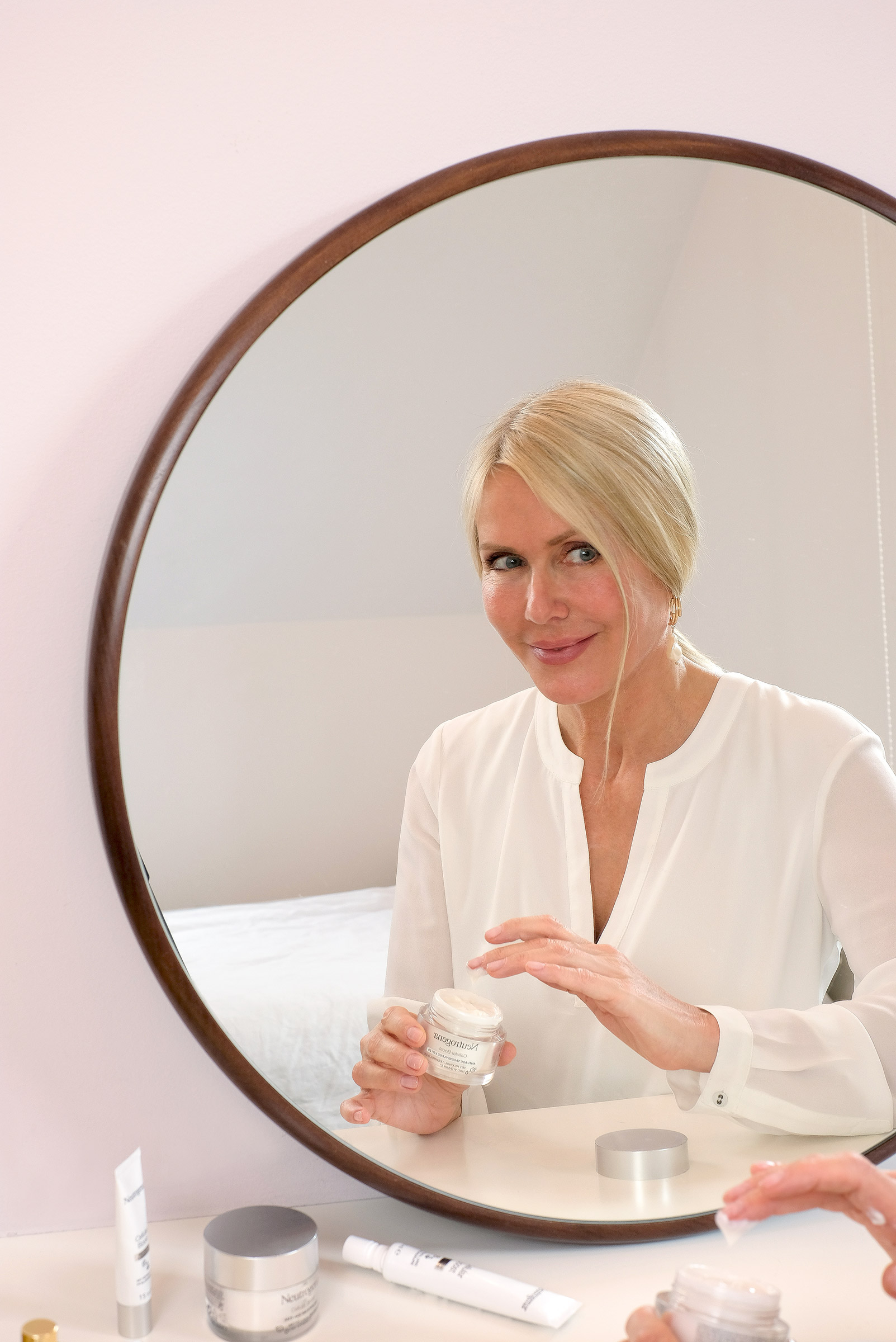 blonde, woman, sitting, in front of a mirror, neutrogena, cellular boost, skincare