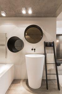 Badezimmer, Zwei Spiegel, rund, Waschsäule, schwarze Armaturen, Fliesen in Holzoptik, Wandheizung, Trend, Blogbeitrag auf lifetimepieces.com