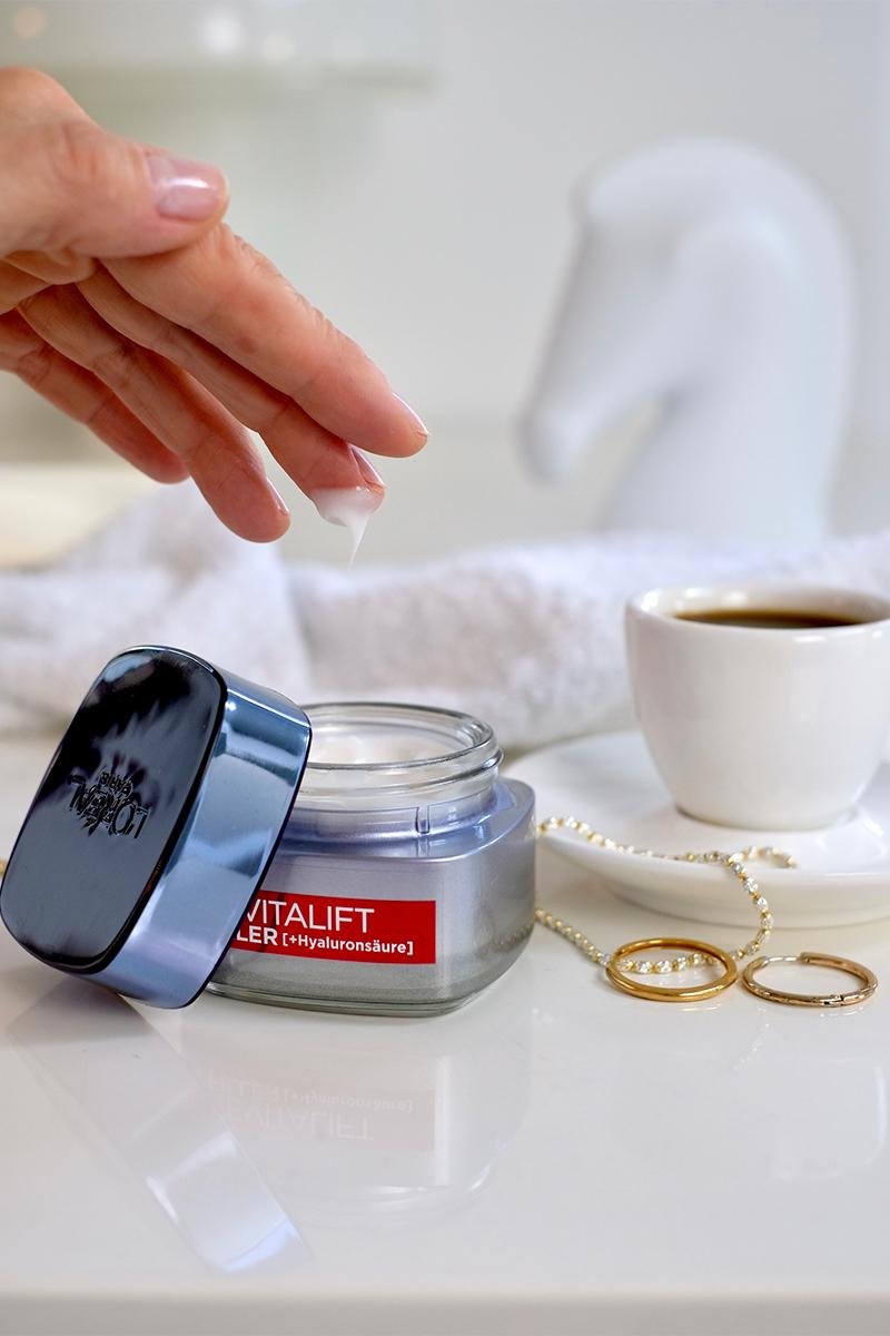 Hand einer Frau entnimmt L'Oréal Revitalift Filler Anti-Falten Tiegel etwas Creme. Daneben steht eine Tasse Espresso auf dem Tisch. Interview über die top zehn Tipps für schöne Haut auf dem Blog lifetime-pieces.com