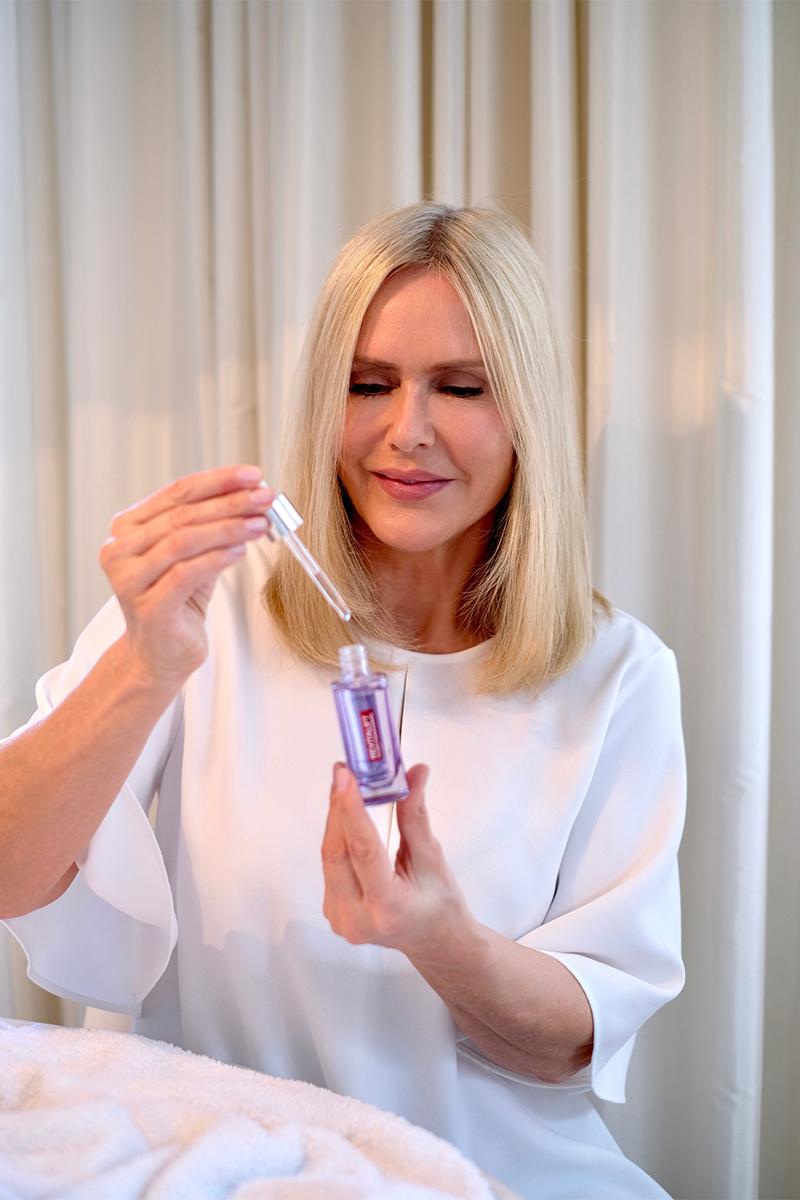 Judith Mosqueira do Amaral, Frau, blond, sitzt am Tisch, hält eine Flasche L'Oréal Revitalift Filler Anti-Falten Serum mit Hyaluronsäure in der Hand, Interview über die top zehn Tipps für schöne Haut auf dem Blog lifetime-pieces.com
