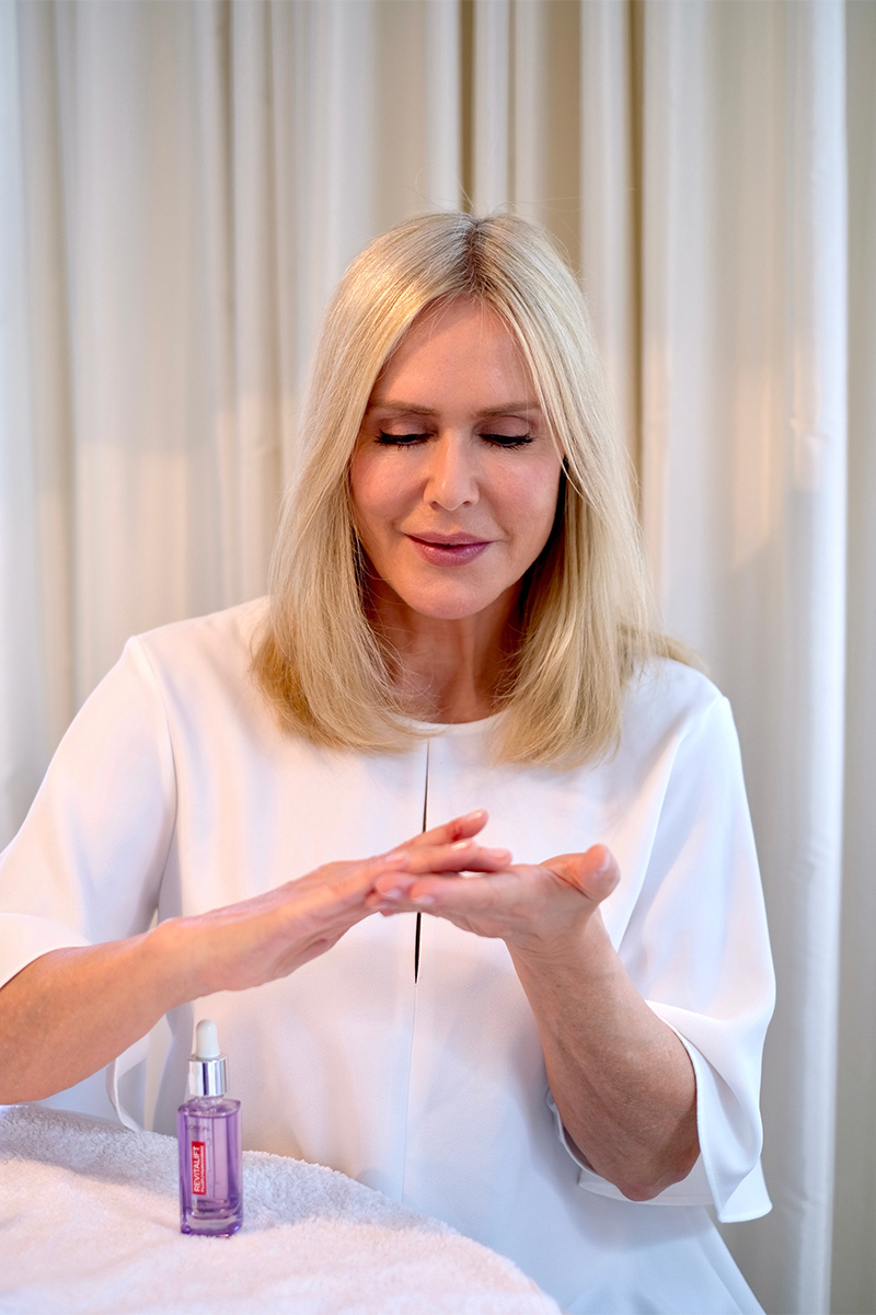 Judith Mosqueira do Amaral, Frau, blond, sitzt am Tisch, verreibt L'Oréal Revitalift Filler Anti-Falten Serum mit Hyaluronsäure in den Händen, Interview über die top zehn Tipps für schöne Haut auf dem Blog lifetime-pieces.com