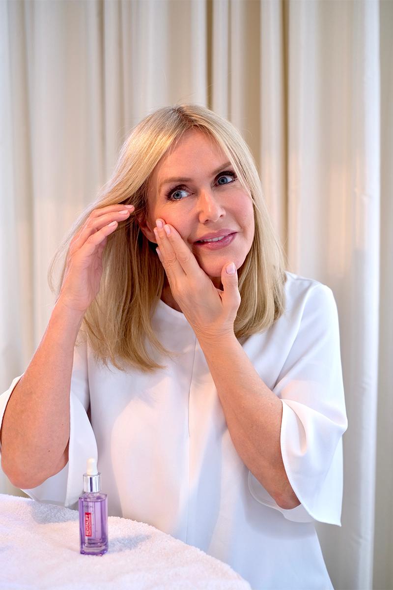 Judith Mosqueira do Amaral, Frau, blond, sitzt am Tisch, trägt L'Oréal Revitalift Filler Anti-Falten Serum mit Hyaluronsäure auf ihr Gesicht auf, Interview über die top zehn Tipps für schöne Haut auf dem Blog lifetime-pieces.com