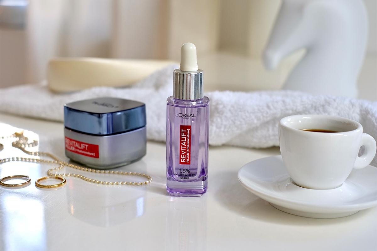 Auf einem Tisch liegen L'Oréal Revitalift Filler Anti-Falten Creme und Serum mit Hyaluronsäure, eine Tasse Espresso, ein weißes Handtuch Ohrringe und eine Halskette. Interview über die top zehn Tipps für schöne Haut auf dem Blog lifetime-pieces.com
