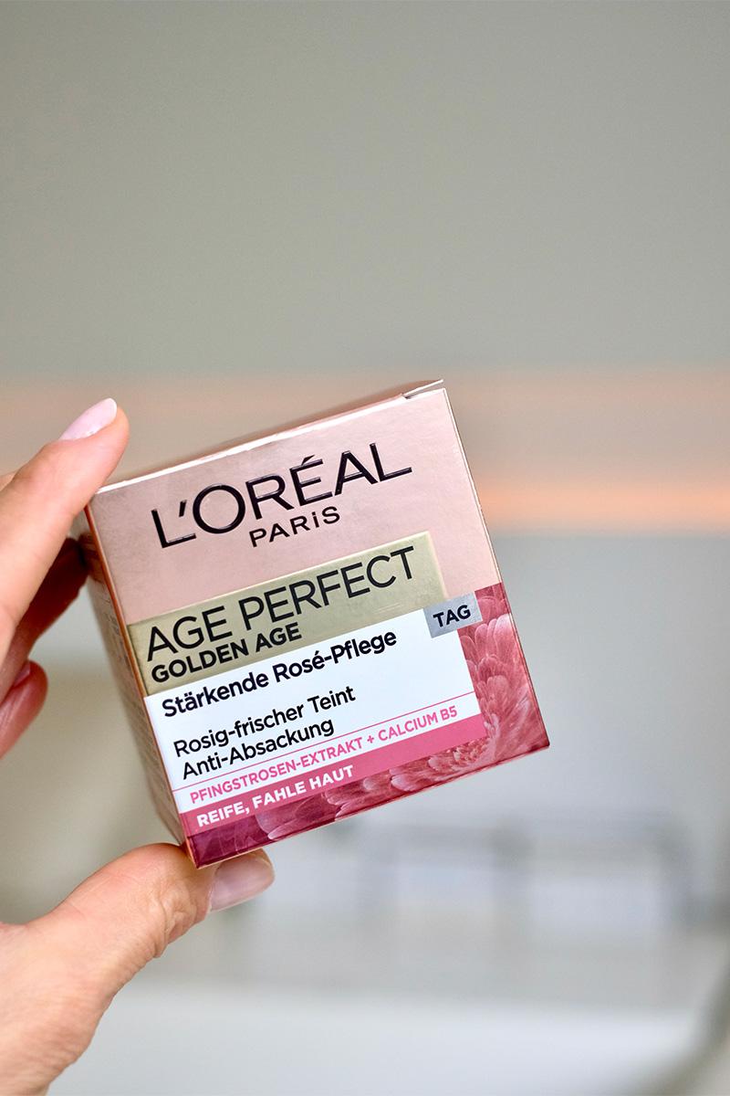 Finger halten die Verpackung der Age Perfect Golden Age Hautcreme. Blogbeitrag auf lifetime-pieces.com über die größten Kosmetik Mythen, wie überflüssige Verpackung, Tierversuche und wie nötig Hautpflege überhaupt ist.
