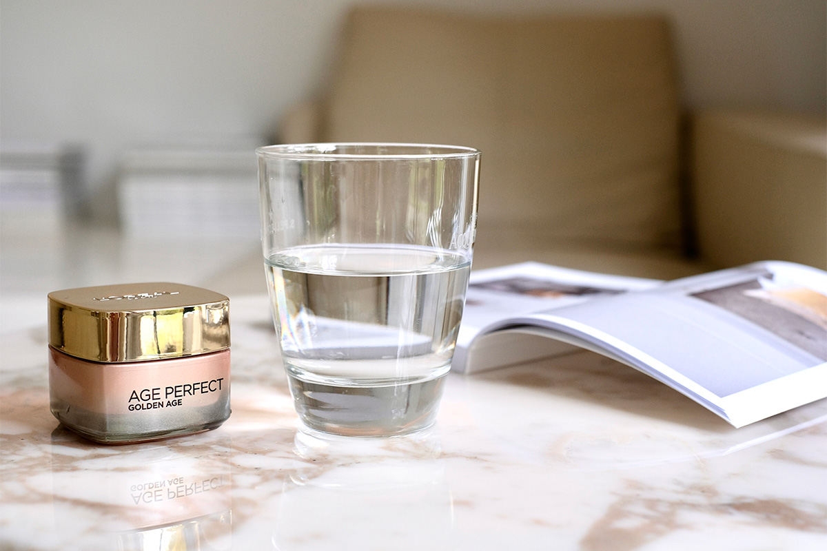 Ein aufgeschlagenes Buch, Wasserglas und die Age Perfect Golden Age Hautpflege stehen auf einem Marmortisch. Bild aus dem Blogbeitrag auf lifetime-pieces.com über die größten Kosmetik Mythen, wie überflüssige Verpackung, Tierversuche und wie nötig Hautpflege überhaupt ist.