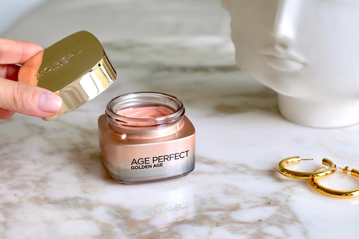 Frauenhand öffnet einen Tiegel Age Perfect Golden Age Hautpflege, die auf einem Marmortisch steht. Bild aus dem Blogbeitrag auf lifetime-pieces.com über die größten Kosmetik Mythen, wie überflüssige Verpackung, Tierversuche und wie nötig Hautpflege überhaupt ist.