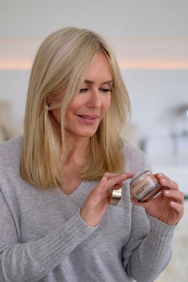 Blonde Frau in grauem Pullover hält einen Creme Tiegel in der Hand und greift mit den Fingern der anderen Hand hinein. Bild aus dem Blogbeitrag auf lifetime-pieces.com über die größten Kosmetik Mythen, wie überflüssige Verpackung, Tierversuche und wie nötig Hautpflege überhaupt ist.