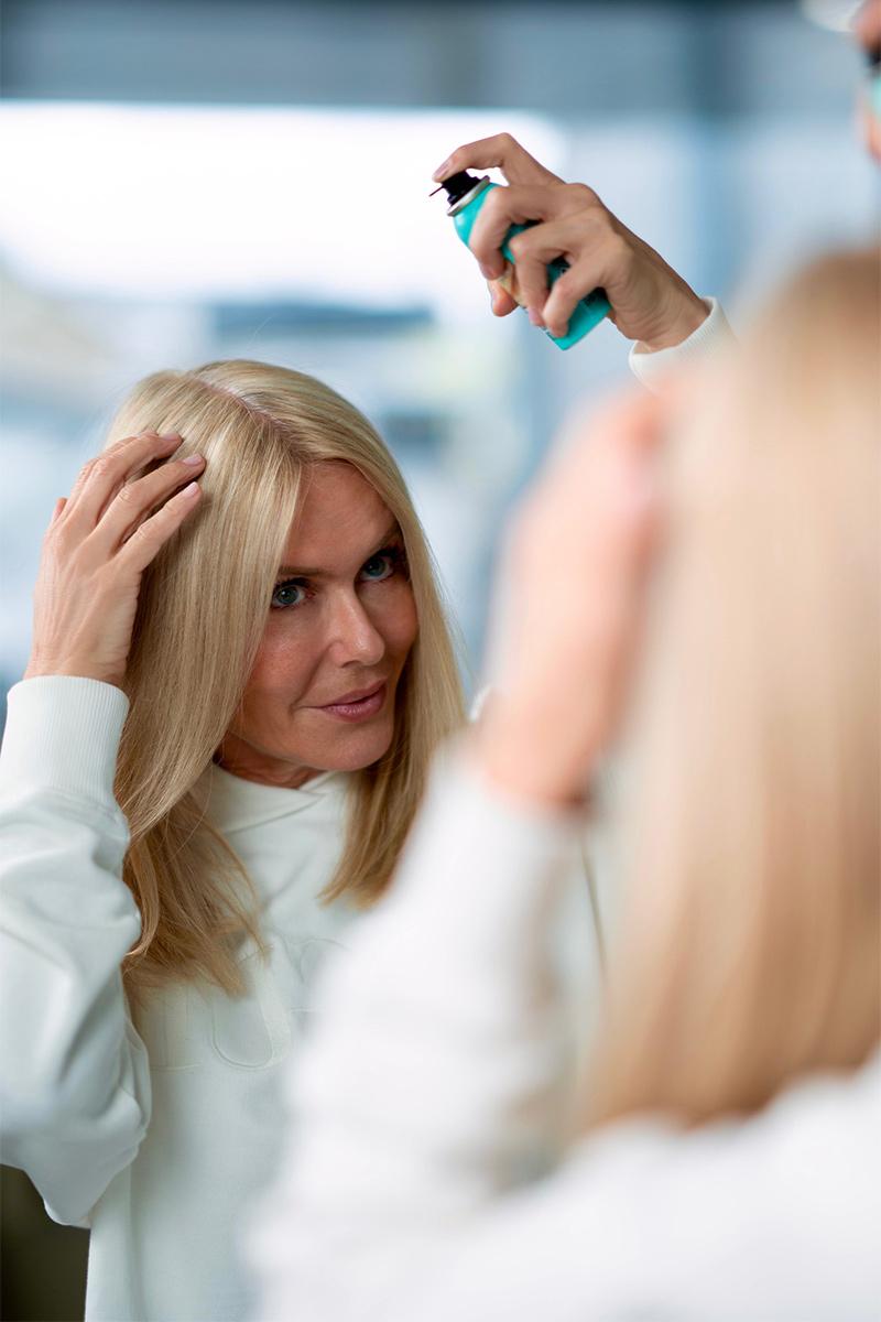 Blonde Frau steht vor dem Spiegel und sprüht ihren grauen Haaransatz mit Magic Retouch ein